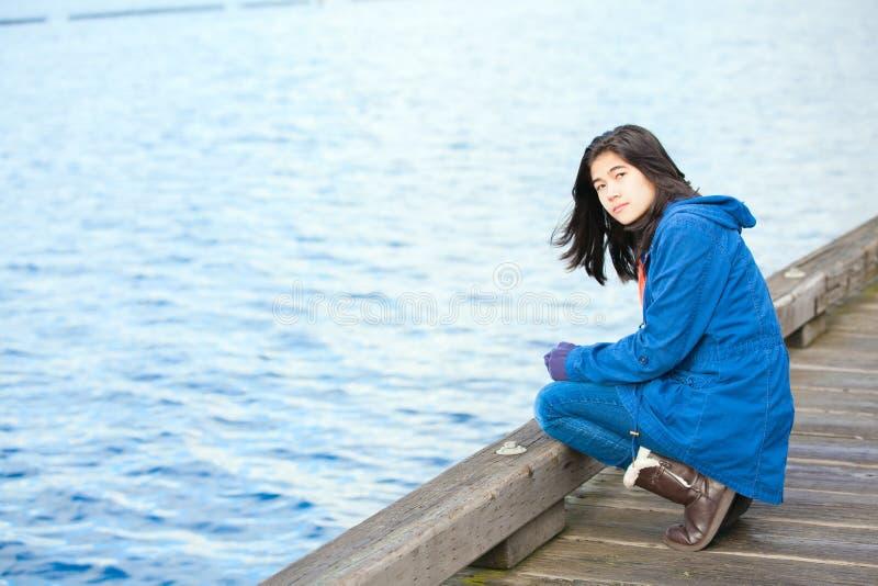 Унылая, сиротливая biracial предназначенная для подростков девушка на деревянной пристани водой стоковые фото