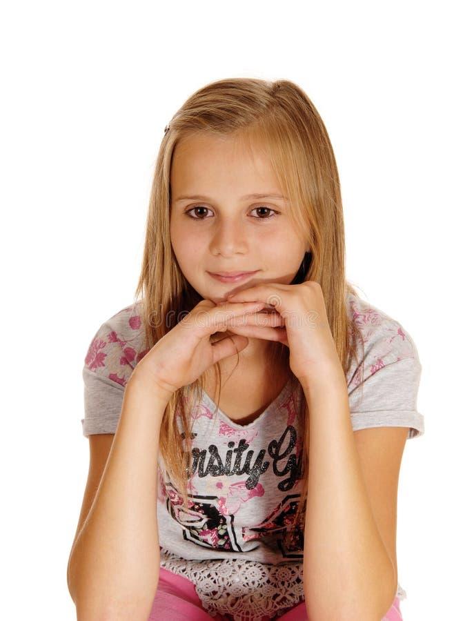 Унылая смотря маленькая девочка сидя на стуле стоковое изображение rf