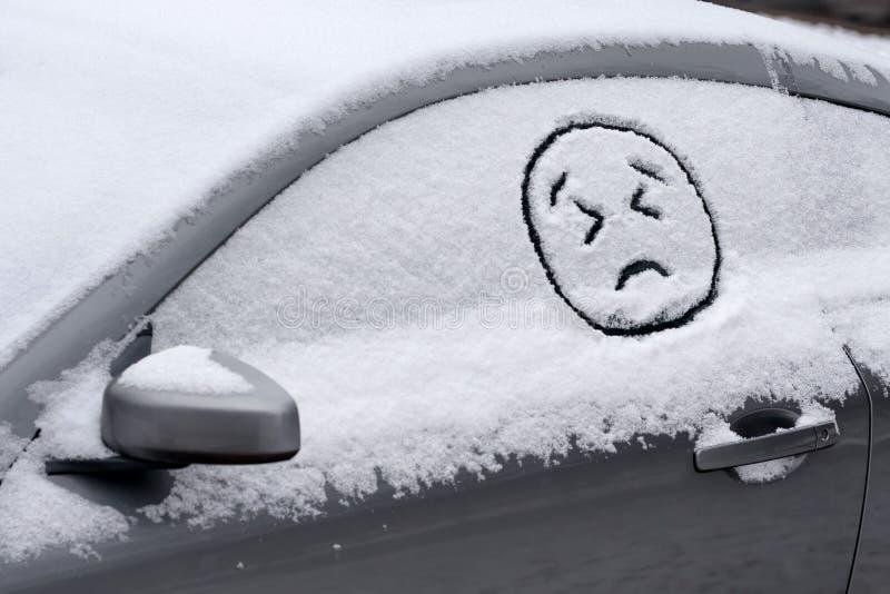 Унылое/сердитое Emoji смотрит на вычерченное в окне автомобиля покрытом с снегом стоковое фото rf