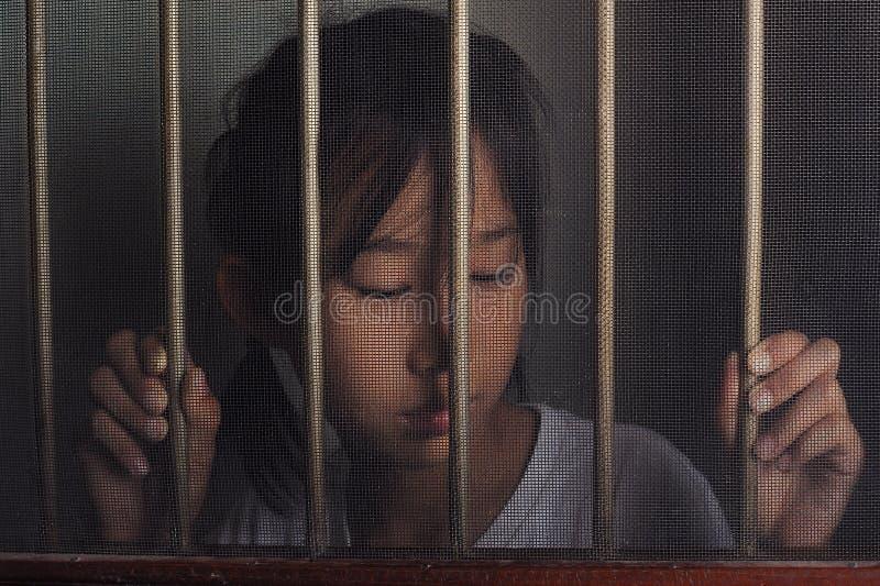 Унылый азиатский ребенок стоя за окном экрана провода в темном m стоковое фото rf