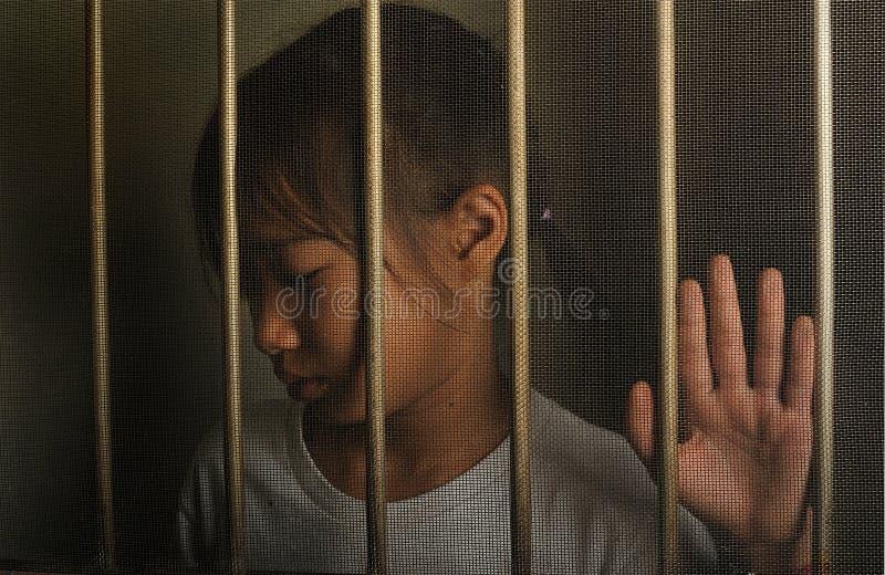 Унылый азиатский ребенок стоя за окном экрана провода Несчастный стоковые фото