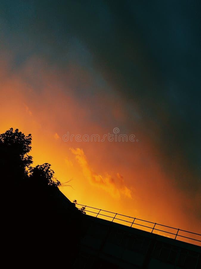Унылый заход солнца апельсина и сини над городом стоковые изображения rf