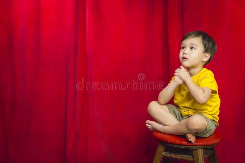Унылый мальчик смешанной гонки сидя на табуретке перед занавесом стоковая фотография rf