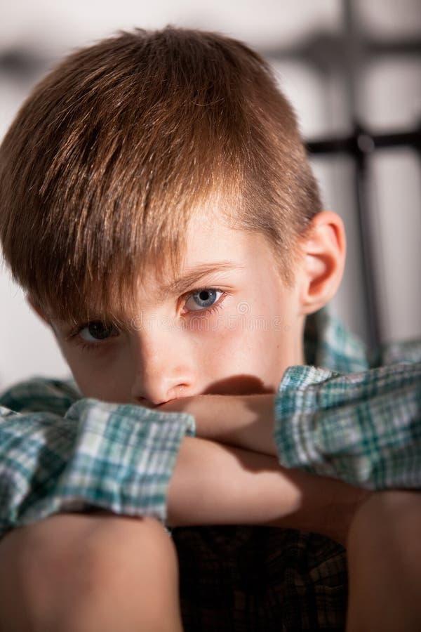 Унылый молодой мальчик при колени вверх смотря камеру стоковые фотографии rf