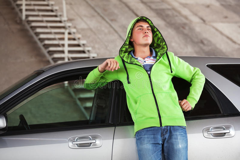 Унылый молодой человек стоя рядом с его автомобилем внешним стоковая фотография rf
