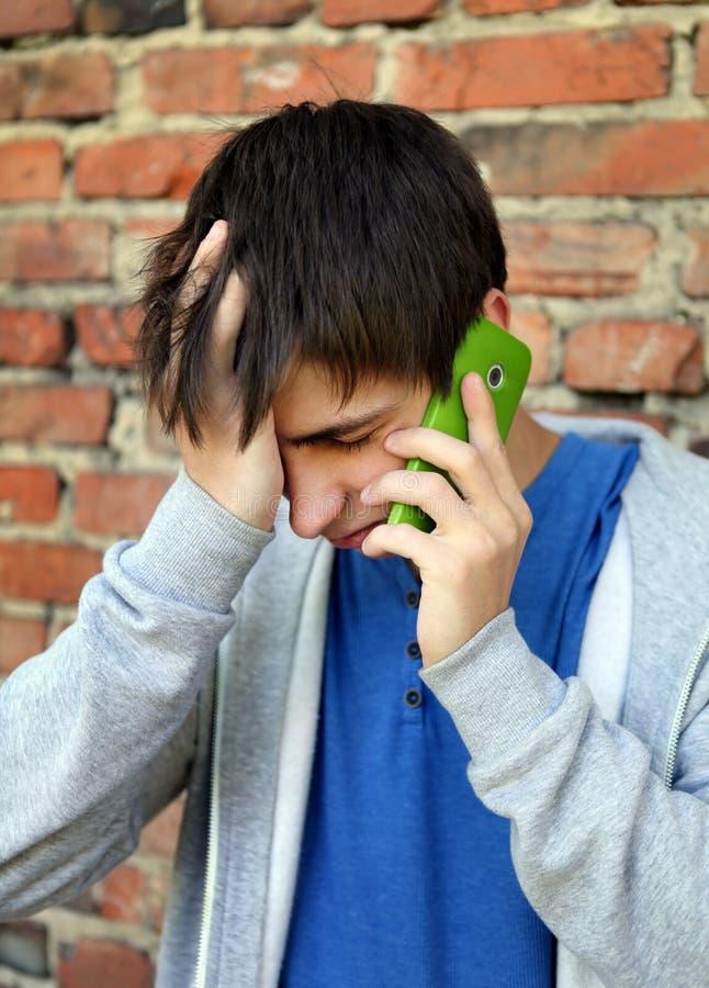 Унылый молодой человек с мобильным телефоном стоковые изображения rf