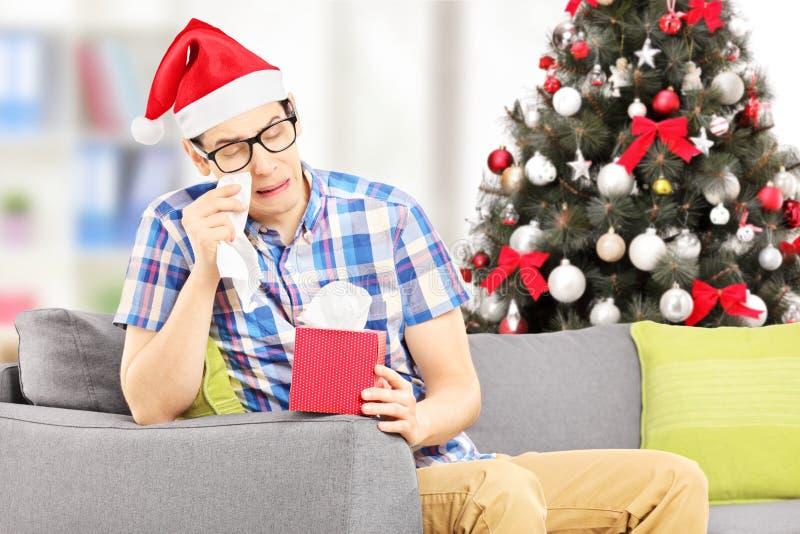 Унылый мужчина на софе обтирая его наблюдает с рождественской елкой в ба стоковое фото rf