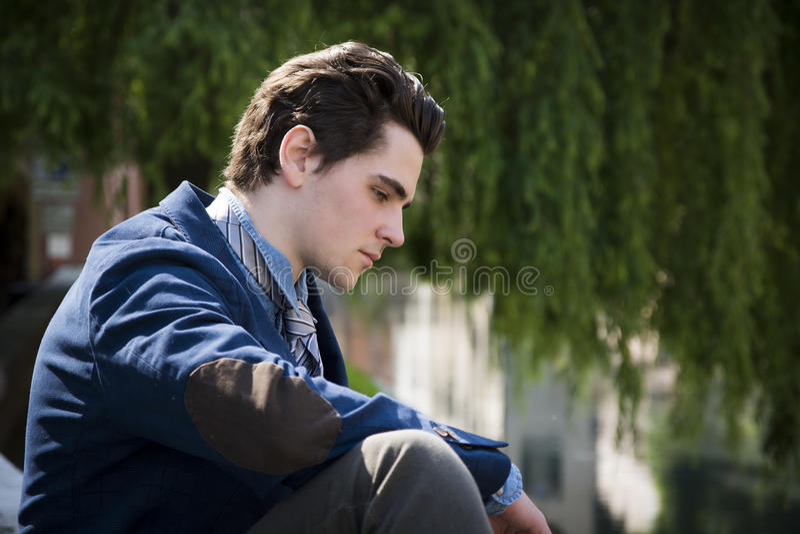 Унылый, потревоженный сидеть молодого человека внешний в городке стоковое изображение