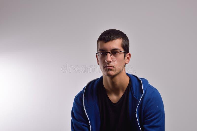 Унылый подросток при голубая фуфайка стоя против пакостной стены стоковое фото rf