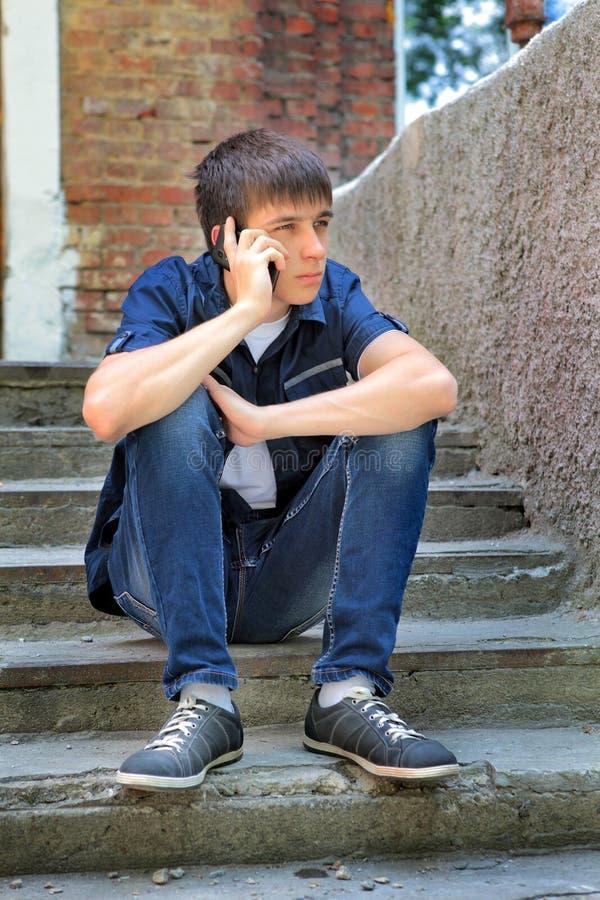Унылый подросток с мобильным телефоном стоковое фото