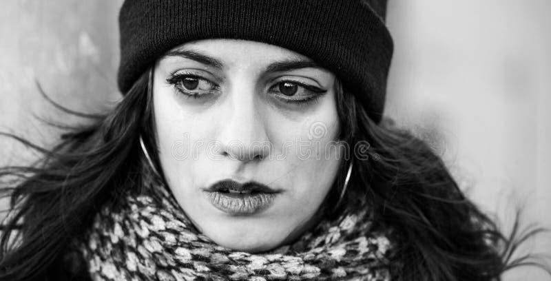 Унылый, плача красивый подросток с черной шляпой - черно-белой съемкой стоковое изображение