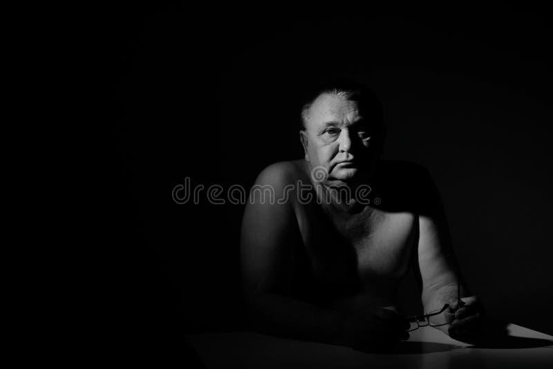 Унылый старший человек сидя с стеклами над чернотой стоковая фотография rf