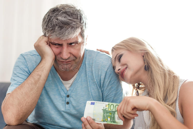 Унылый супруг дает 100 евро к жене golddigger стоковое изображение