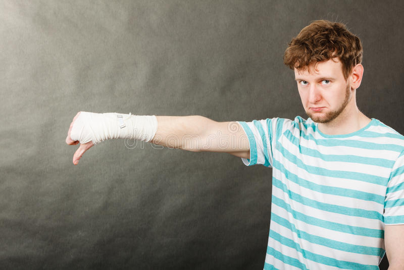 Унылый человек показывая большой палец руки вниз перевязанной рукой стоковые изображения rf