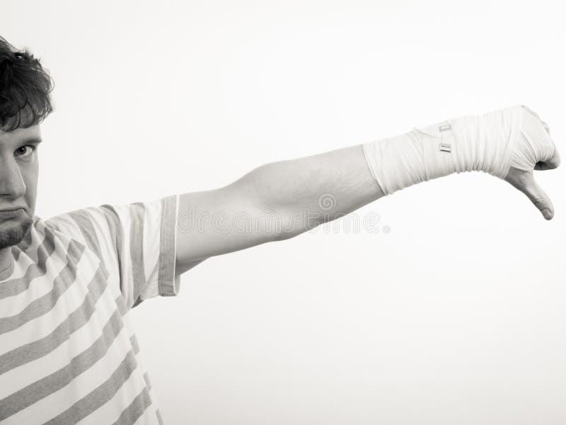 Унылый человек показывая большой палец руки вниз перевязанной рукой стоковая фотография rf