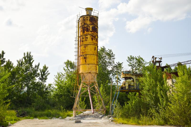 Упаденное ржавое фото концепции индустрии в получившейся отказ фабрике цемента с достигшими возраста strucures бетона и металла g стоковая фотография rf