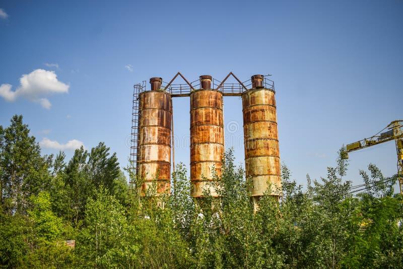 Упаденное ржавое фото концепции индустрии в получившейся отказ фабрике цемента с достигшими возраста strucures бетона и металла g стоковая фотография