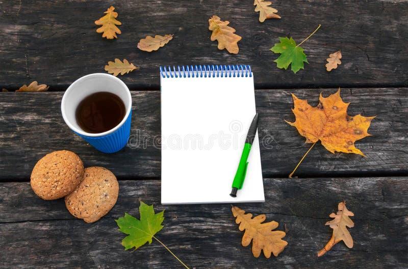 Упаденные листья осени на старой деревянной предпосылке, горячая чашка кофе, домодельные печенья овсяной каши, блокнот, ручка Вре стоковое фото