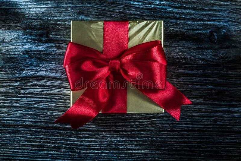 Упакованная золотая подарочная коробка на деревянной доске стоковое изображение