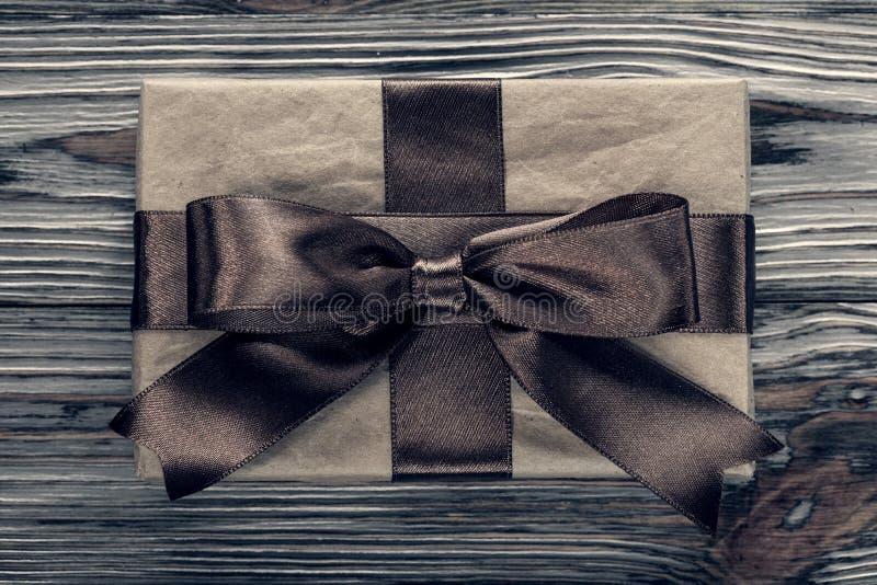 Упакованная коричневая подарочная коробка на винтажной деревянной доске стоковые фото