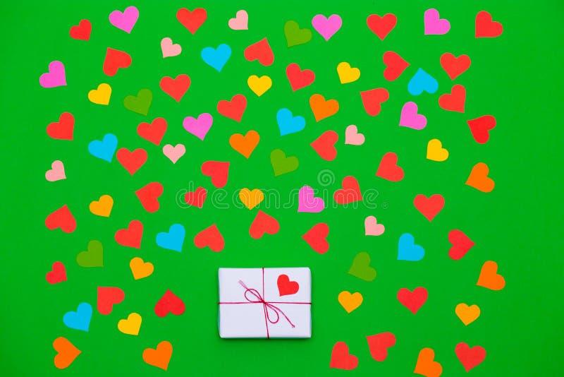 Упакованная подарочная коробка на зеленой предпосылке с много пестротканых сердец вокруг стоковое фото