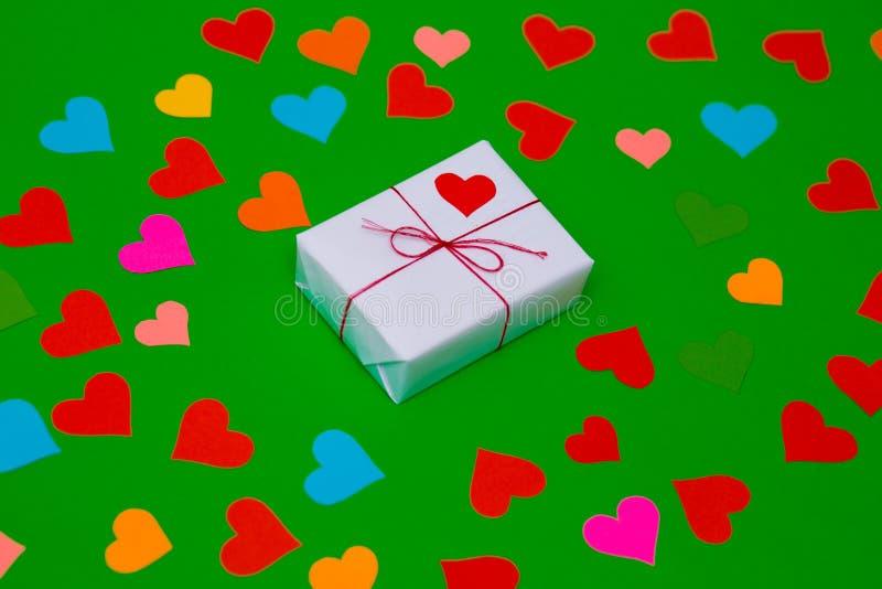 Упакованная подарочная коробка на зеленой предпосылке с много пестротканых сердец вокруг стоковое изображение
