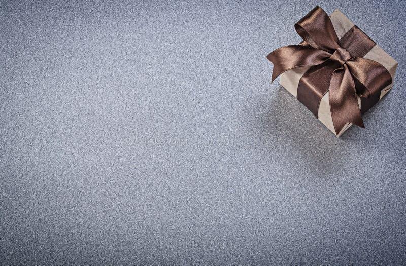 Упакованная присутствующая коробка в коричневой бумаге на сером космосе экземпляра предпосылки стоковая фотография rf