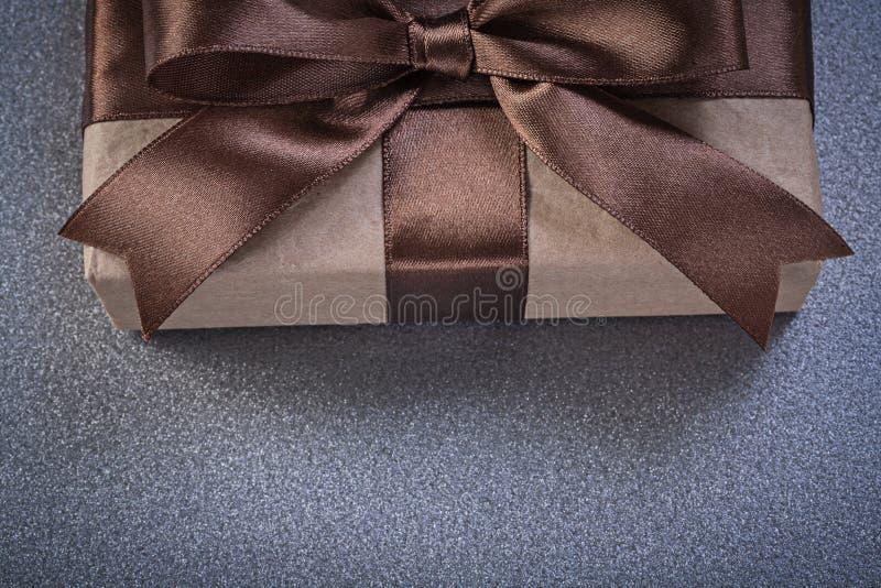 Упакованное присутствующее в коричневой бумаге магазина на сером вид спереди предпосылки стоковое изображение