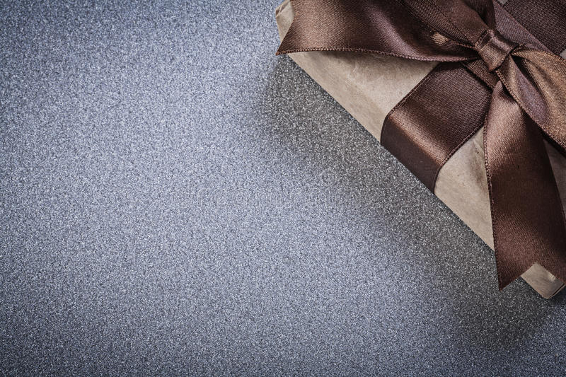 Упакованное присутствующее с коричневым смычком на серых торжествах предпосылки стоковая фотография rf