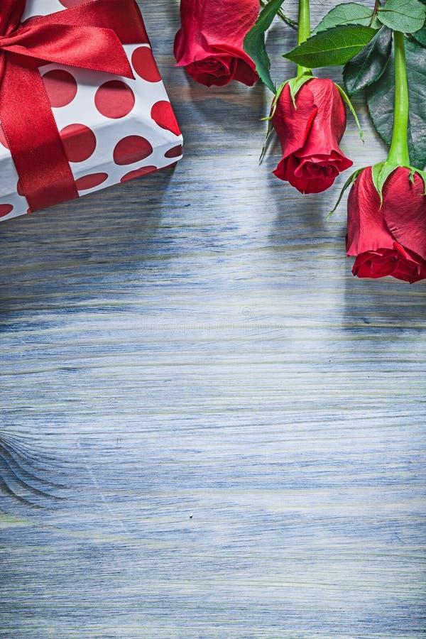 Упакованные красные розы присутствующей коробки ароматичные на праздниках c деревянной доски стоковая фотография