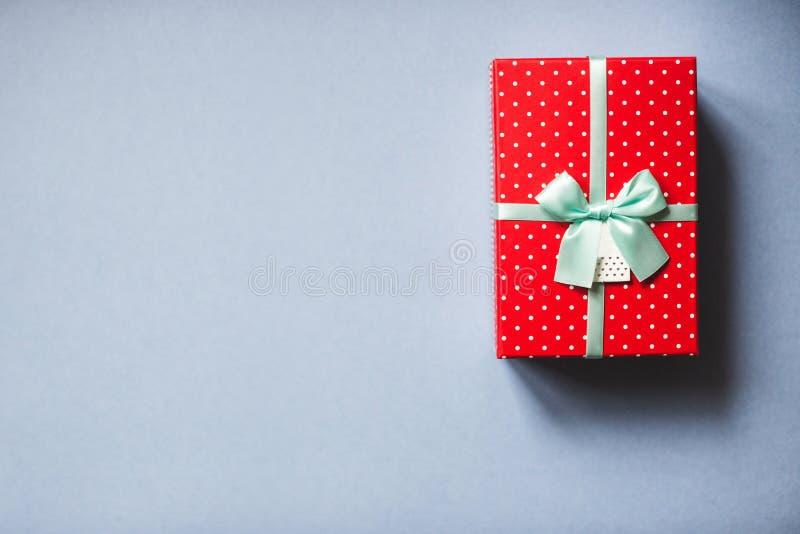 Упакованный красный цвет присутствующий с смычком на голубой предпосылке стоковая фотография rf