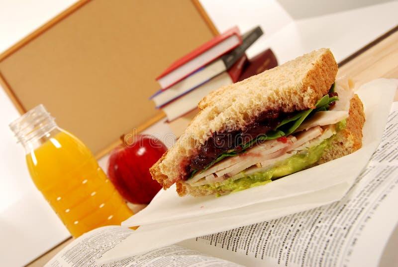 Упакованный школьный обед: сандвич индюка, яблоко, питье на книге словаря в классе стоковое фото rf