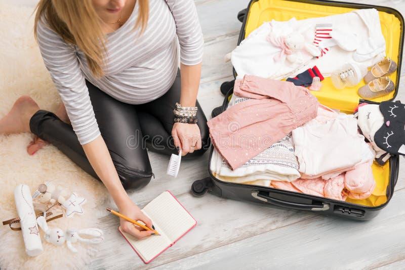 Упаковка беременной женщины для больницы и примечаний принимать стоковое фото rf