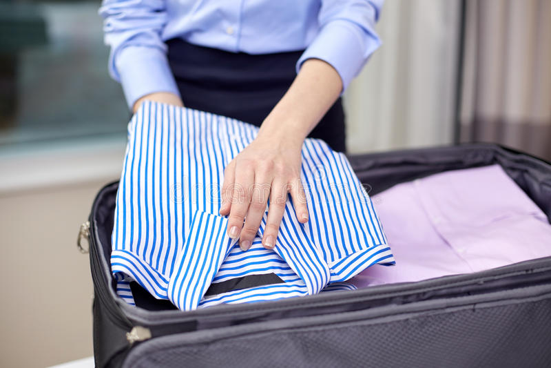 Упаковка коммерсантки одевает в сумку перемещения стоковое фото