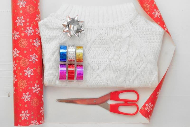 Упаковывая процесс белизны связал свитер Упаковочная бумага с снежинками, покрашенная лента, обхватывает и ножницы горизонтально стоковые фото