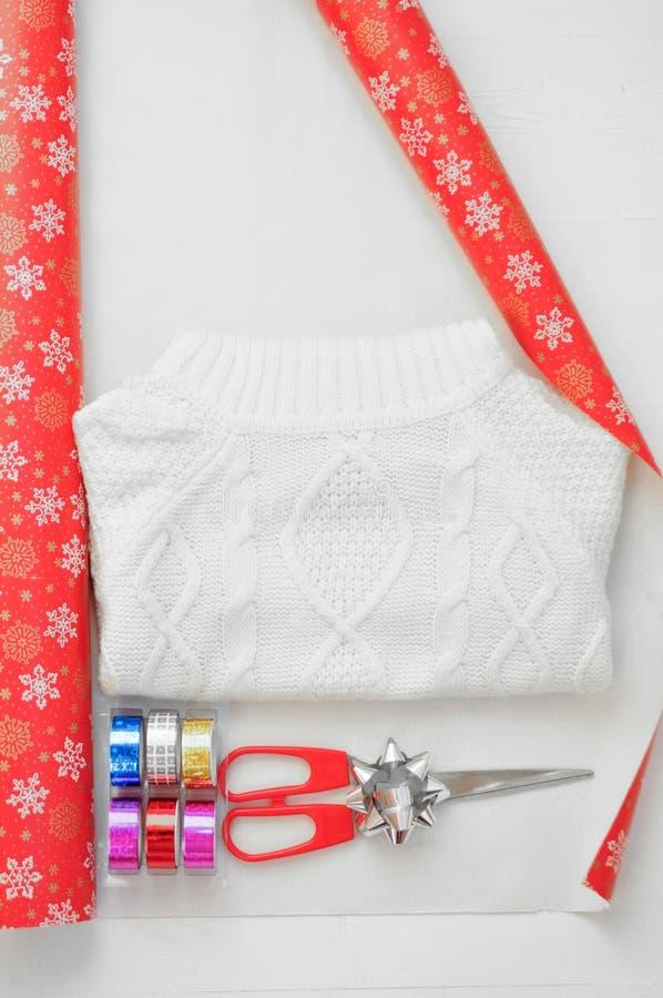 Упаковывая процесс белизны связал свитер Упаковочная бумага с снежинками, покрашенная лента, обхватывает и ножницы vertikal стоковая фотография