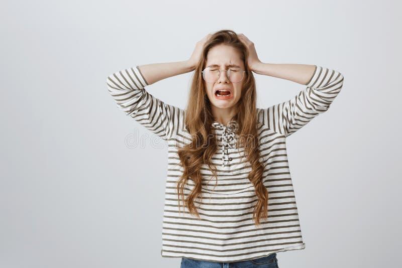 Управление девушки проигрышное чувств, находящся под давлением и стрессом Милая молодая женщина в стеклах держа руки на голове стоковая фотография rf