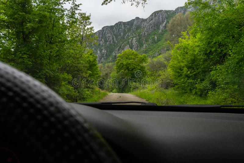 Управлять автомобилем в горе на пути с зеленым лесом и большими утесами Взгляд водителя с черным рулем стоковая фотография