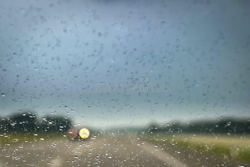 Управлять в дожде на шоссе Запачканные фары причаливая автомобиля как увидено до конца дождю падают на windscreen стоковое фото rf