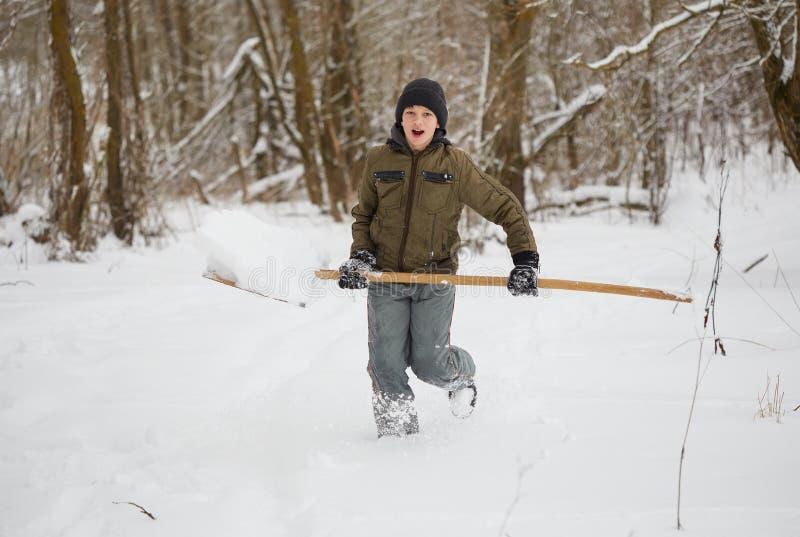 управлять зимой розвальней потехи подросток имея потеху играя с снегом стоковая фотография rf