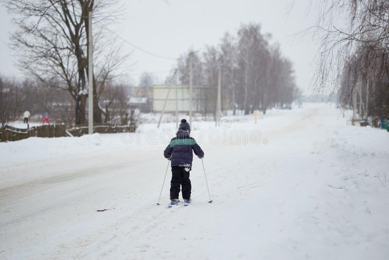 управлять зимой розвальней потехи ребенок катается на лыжах вокруг деревни стоковые фото