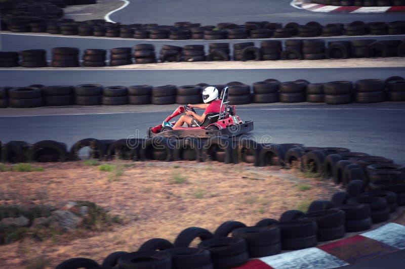Управлять людей идет-kart автомобиль с скоростью в гоночном треке спортивной площадки стоковое фото rf
