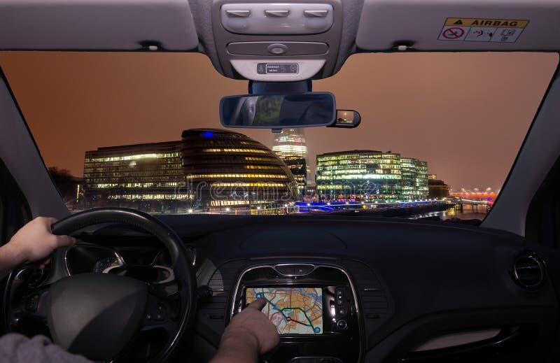 Управляющ используя GPS к городу Лондона на ноче, Великобритания стоковое изображение rf