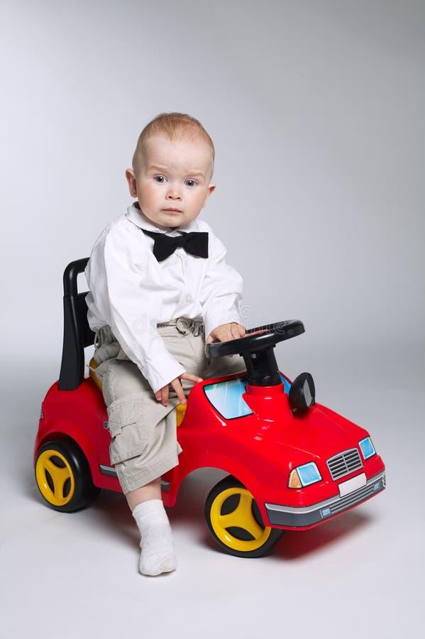 управлять автомобиля мальчика меньшяя игрушка стоковые фото