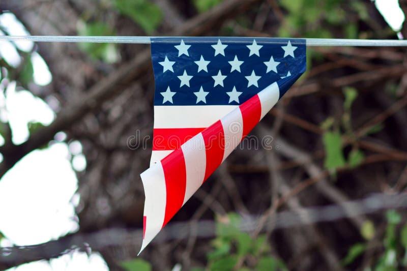 Упрощенный флаг с американскими цветами с красными нашивками и белыми звездами на голубой линии hangingfrom предпосылки стоковые фотографии rf