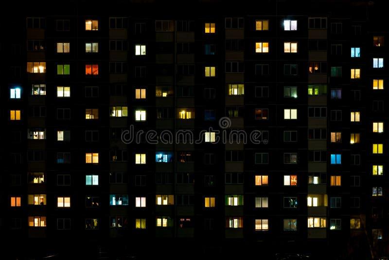 Упущение nighttime света в окнах многоэтажного здания жизнь в большом городе стоковые фото