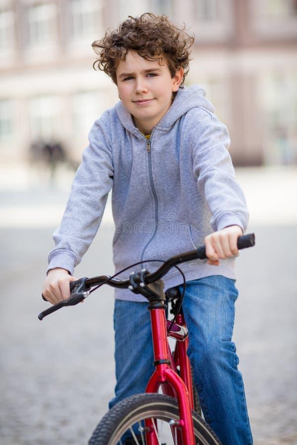 Урбанский велосипед - подросток и велосипед в городе стоковые изображения