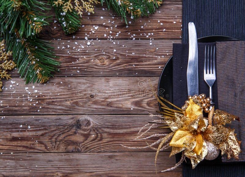 Урегулирование места таблицы рождества с черной салфеткой, плитой, вилкой и ножом, украсило цветок золота и сосну рождества стоковые изображения