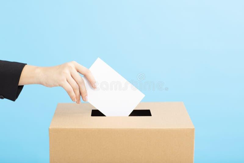Урна для избирательных бюллетеней с решающим голосом персоны на пустом бюллетене голосования стоковые фотографии rf