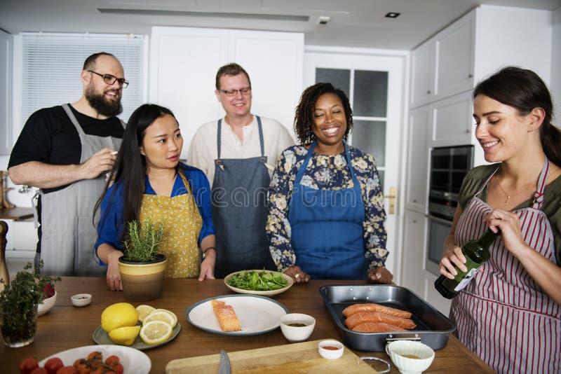 Урок кулинарии разнообразных людей соединяя стоковое изображение rf